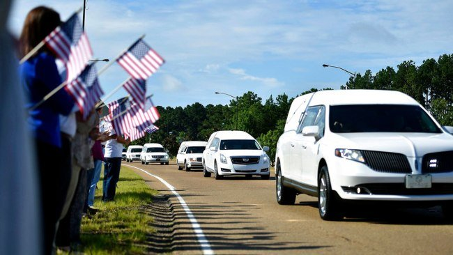 Supporters hold American flags on the side of Airport Road in Jackson, Miss., Thursday, July 13, 2017, as hearses carry the remains of the 16 service members who died in a plane crash in Leflore County, on Monday to the Air National Guard base for their f