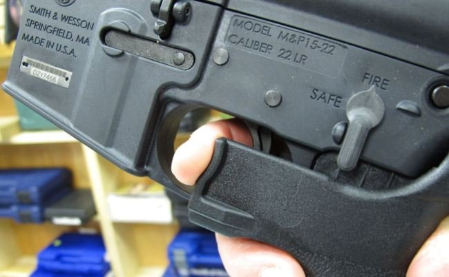 """FILE - In this Feb. 1, 2013, file photo, an employee of North Raleigh Guns demonstrates how a """"bump"""" stock works at the Raleigh, N.C., shop. (AP Photo/Allen Breed, File)"""