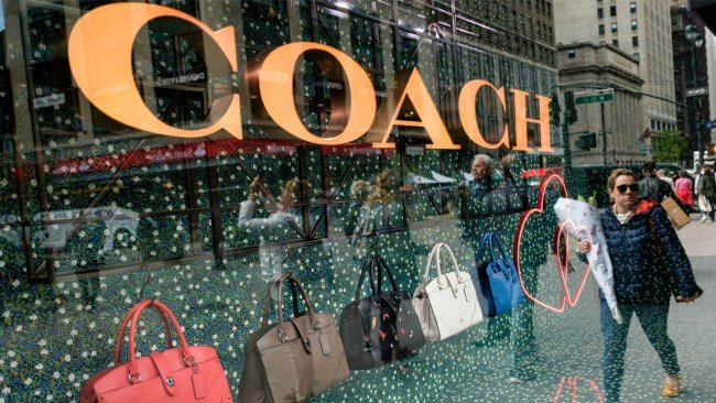 NEW YORK, NY - MAY 12: A woman walks past Coach bags in a window of Macy's flagship store, May 12, 2017 in the Herald Square neighborhood in New York City. (Photo by Drew Angerer/Getty Images)