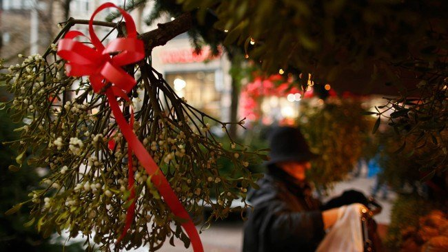 A woman buys mistletoes at a stall on the christmas market in the main pedestrian street on December 7, 2013 in Hamburg, Germany. (Photo by Philipp Guelland/Getty Images)