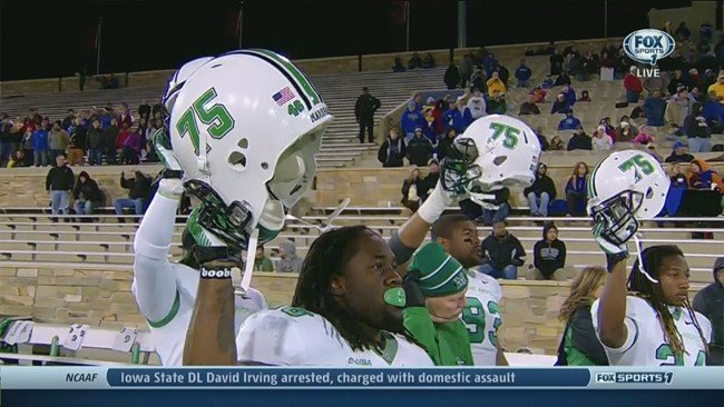 "Herd players at Tulsa holding up ""75"" helmets"