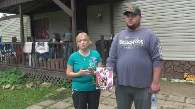 Randy and Trisha Scaff stand outside a relative's home with a picture of Jonathan. The family plans to move out of the home where Jonathan took his own life.